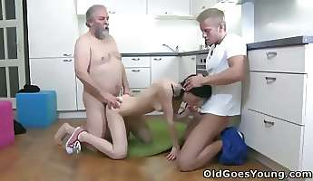 Karina kneels before both of her men and takes their cum all over her mouth and tits